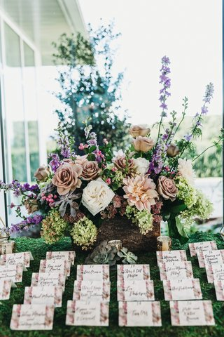 rows-of-escort-cards-with-floral-borders-in-front-of-colorful-flower-arrangement