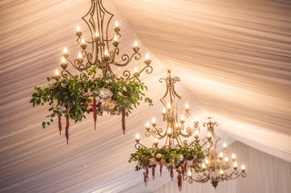 tented-reception-with-drapery-chandeliers-with-greenery-and-florals