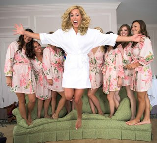 bride-in-white-robe-jumping-from-couch-bridesmaids-in-flower-print-pink-robes