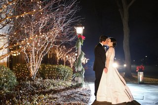 bride-in-oscar-de-la-renta-wedding-dress-kissing-groom-at-night-around-christmas-decorations