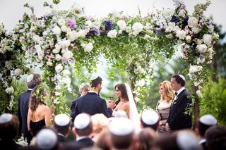 outdoor-jewish-wedding-ceremony-yarmulke-on-guests-flower-chuppah-outdoor-ceremony-purple-white-pink