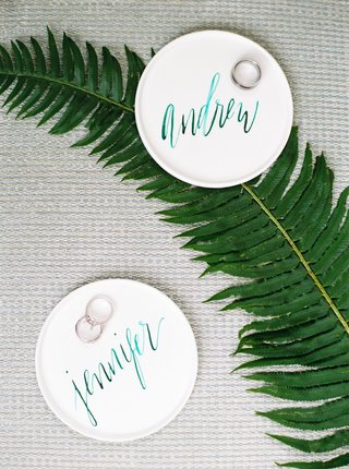 wedding-rings-on-personalized-teal-modern-calligraphy-on-ring-holder-trays-white-on-fern-leaf