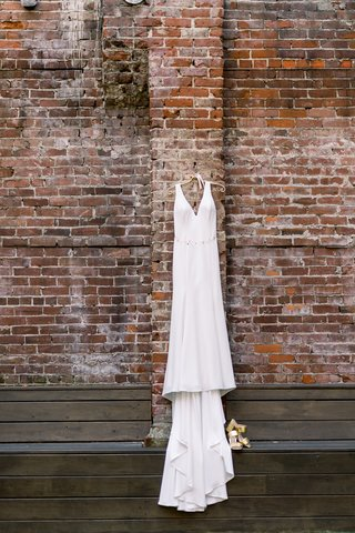 v-neck-allure-bridal-gown-of-silk-crepe-hanging-on-brick-wall
