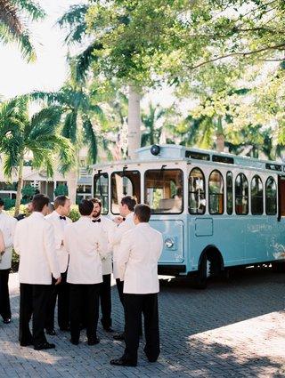 groomsmen-in-white-tuxedo-jackets-standing-by-light-blue-trolley-car-for-wedding-ceremony-transport
