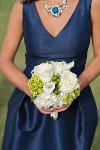 bridesmaid-in-a-sleeveless-navy-blue-dress-holds-a-bouquet-of-white-roses-hydrangeas-calla-lilies
