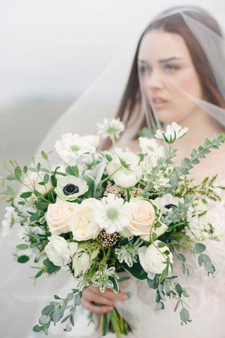 a-bride-holds-a-lush-bouquet-of-green-foliage-surrounding-white-and-blush-flowers-on-a-beach