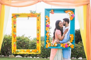 mehndi-in-orange-county-south-asian-couple-photo-booth-inspiration-bright-frames-with-flowers