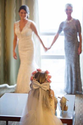 flower-girl-watching-bride-get-ready-in-suite