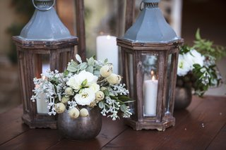ranch-wedding-reception-with-white-flowers-greenery-in-coppertone-vases-wood-lanterns