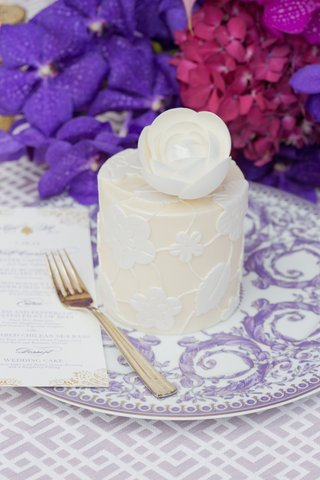 personal-white-wedding-cake-with-flower-and-leaf-design-topped-with-a-sugar-flower-on-versace-plate