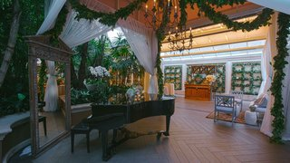 grand-piano-next-to-rustic-mirror-lounge-area-garlands-of-greenery-chandeliers-trellis-wall