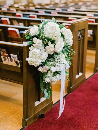 traditional-church-ceremony-wood-pews-flower-arrangments-white-hydrangea-rose-tulip-ribbon-greenery