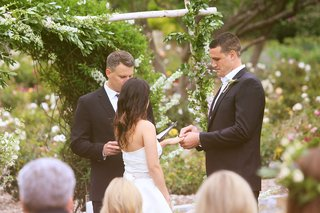 bride-and-groom-exchange-rings-in-front-of-greenery-arbor