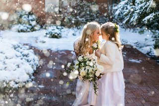 bride-in-gregory-ellenberg-crouches-down-with-her-daughter-in-fur-coat-in-the-snow