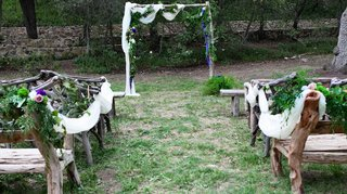 outdoor-wedding-ceremony-at-the-oak-canyon-ranch-with-guests-benches-made-of-wood-planks-and-branche