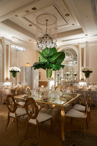 wedding-reception-tall-centerpiece-banana-leaves-in-vase-with-white-roses-at-base-gold-chairs-table