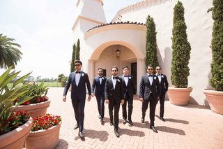 groom-groomsmen-black-tuxedos-walking-forward-pelican-hill-newport-beach-southern-california