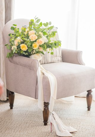 wedding-bouquet-on-chair-at-bacara-santa-barbara-greenery-yellow-rose-peach-white-flowers-ribbon