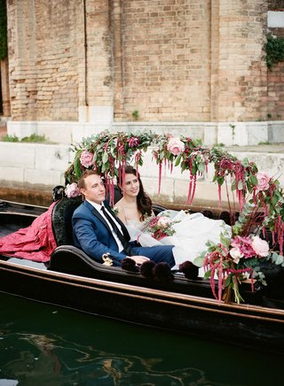 bride-in-wedding-dress-groom-in-navy-suit-inside-gondola-boat-venice-italy-decorated-flowers