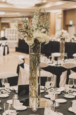 tall-glass-vase-filled-with-twigs-gold-leaves-and-white-flowers