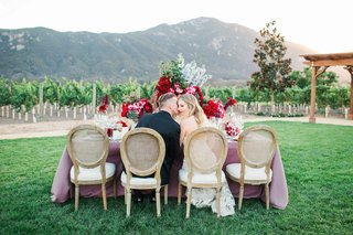 bride-and-groom-kiss-at-romantic-rustic-table-pink-table-linens-red-flowers-california-vineyard