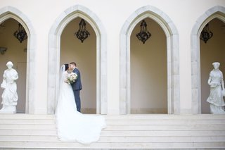 bride-and-groom-kiss-on-steps-of-chateau-in-houston-texas-wedding-venue-ideas