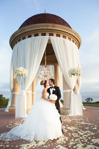 newlyweds-kiss-under-dome-pelican-hill-resort-newport-beach-california-pnina-tornai-dress-drapery