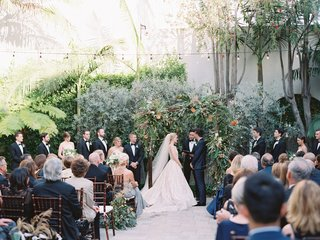 bride-and-groom-under-wood-arbor-greenery-bistro-lights-guests-in-wood-chairs-white-cushions