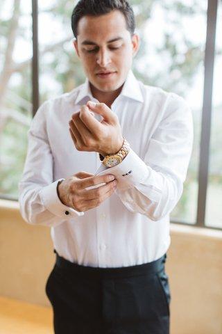 groom-fixing-cufflinks-gold-watch-white-dress-shirt-black-pants-embroidery-california
