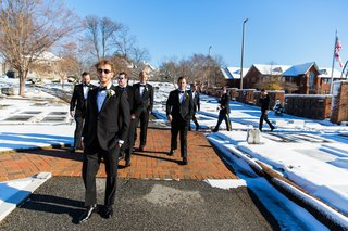 groom-in-brooks-brothers-tuxedo-sunglasses-walks-with-groomsmen-through-snow