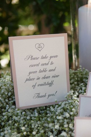 sign-with-instructions-about-escort-cards-on-bed-of-babys-breath