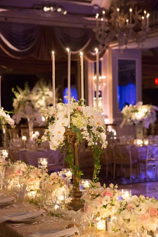 a-tall-candelabrum-featuring-cascading-green-foliage-and-white-orchid-flowers-on-long-table