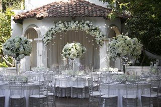 outdoor-wedding-reception-with-white-flowers-clear-chairs-and-silver-details