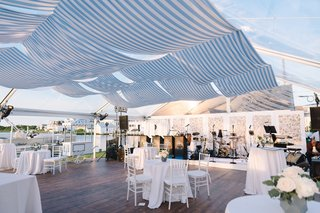 waterfront-tent-wedding-white-and-blue-decorations-striped-awning-shade-for-clear-top-tent-live-band