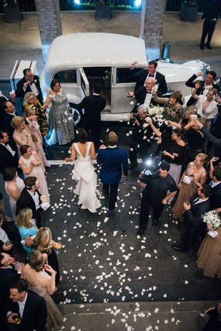 bride-and-groom-walking-toward-classic-white-getaway-car-through-pathway-of-guests-flower-petals