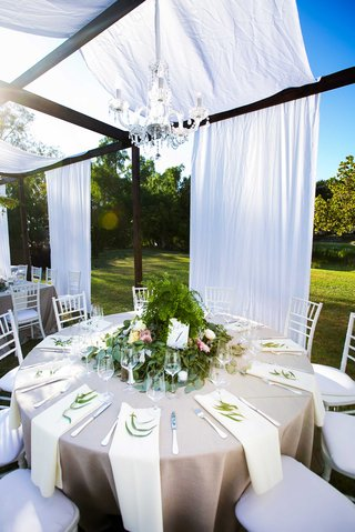 a-round-tablescape-champagne-colored-linens-overflowing-foliage-floral-arrangement-chandelier