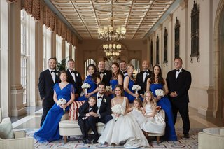 bride-in-anne-barge-wedding-dress-groom-and-groomsmen-in-tuxedos-bridesmaids-bright-blue-dresses