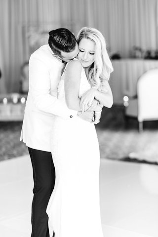 black-and-white-photo-of-bride-and-groom-on-dance-floor-hugging-groom-kissing-bride-neck-reception