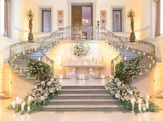 wedding-reception-grand-staircase-greenery-muted-flowers-candles-iron-rail-double-staircase