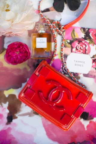small-red-coco-chanel-purse-on-pink-floral-table-linen-and-other-chanel-products-chanel-no-5-perfume
