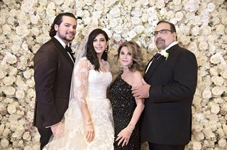 family-wedding-portrait-in-front-of-flower-wall-bride-in-vera-wang