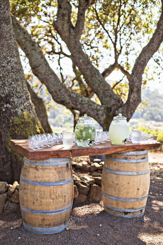 wedding-ceremony-outdoor-water-and-lemonade-station-wine-barrels-wood-decor-under-tree