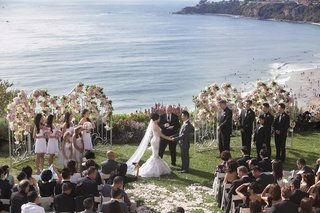 bride-and-groom-at-oceanfront-ceremony-in-front-of-white-gates