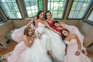 brie-and-bridesmaids-in-morilee-pose-draped-over-each-other-at-windo-seat