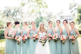 bride-with-bridesmaids-in-mint-blue-green-dresses-sheer-necklines-coral-peony-bouquets-updos