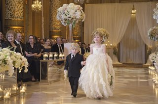 flower-girl-in-full-ruffled-skirt-holding-hands-with-younger-ring-bearer-in-black-suit