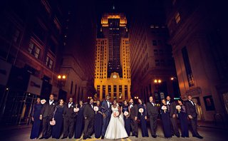 bride-and-groom-in-navy-tuxedo-with-bridesmaids-in-blue-dresses-and-groomsmen-in-tuxes-in-chicago
