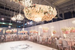 wedding-reception-chandeliers-and-flowers-floating-over-custom-dance-floor-pink-tables