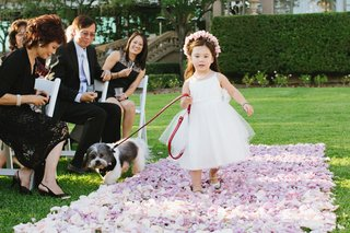flower-girl-walks-down-purple-petal-aisle-with-dog-on-leash