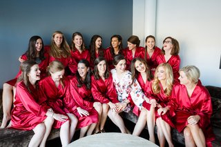bride-in-floral-print-robe-and-bridesmaids-in-red-robes-while-getting-ready-bridal-suite